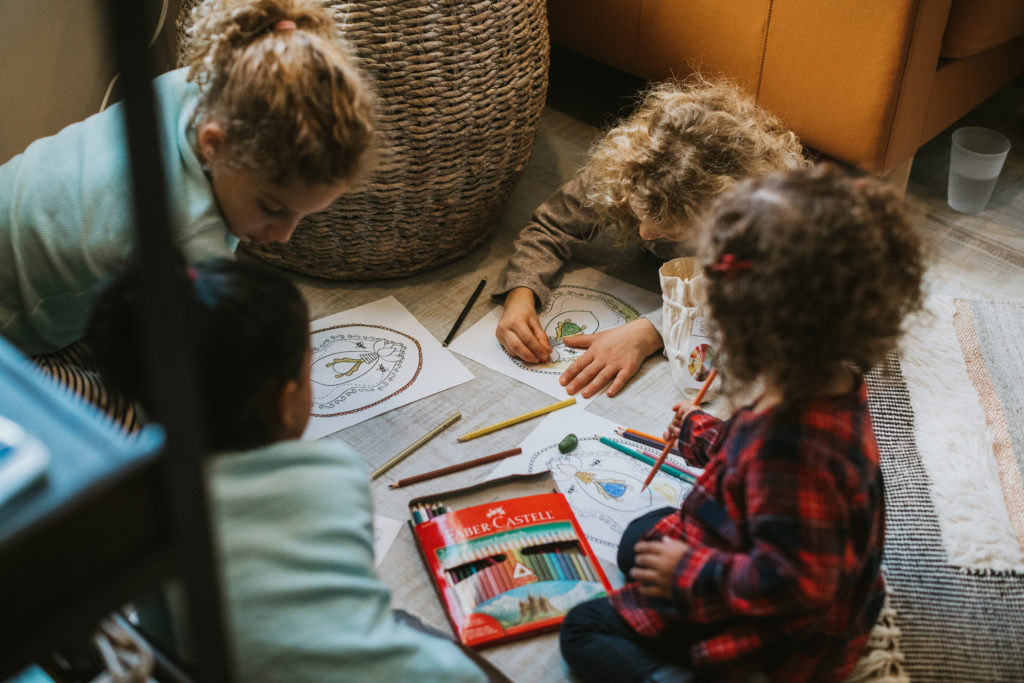 Young children drawing in coloring books